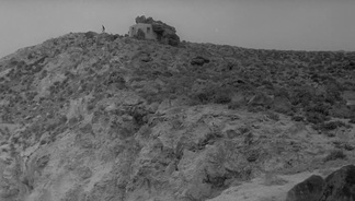 Still of a distant figure on the island's horizon from Antonioni's L'avventura