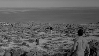 Still of a rocky landscape with people scattered across it from Antonioni's L'avventura