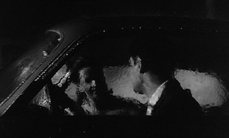 Still from Antonioni's La notte showing Lidia inside a car on a rainy night.