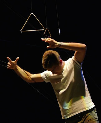 A white man in a white t-shirt grasps ahold of threads suspending musical triangles in the air